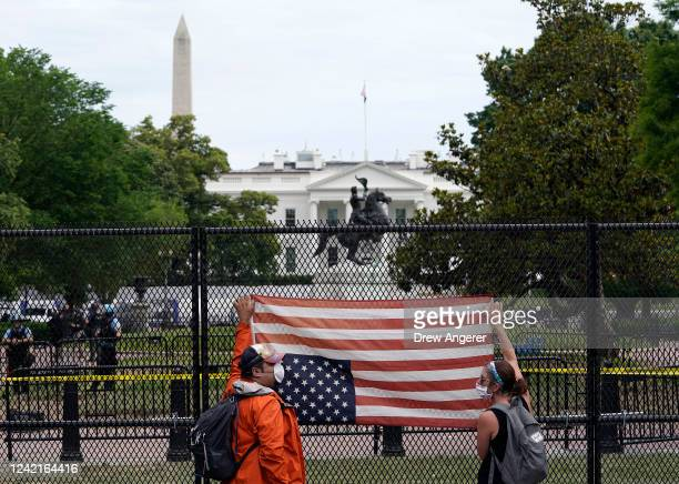 Demonstrators hold an upside down American flag against a tall fence at Lafayette Parknear the White House while protesting against police brutality...