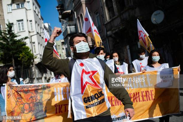 Demonstrators hold banner and flags during a May Day rally marking the international day of the worker in Istanbul, on May 1, 2021. - With the...