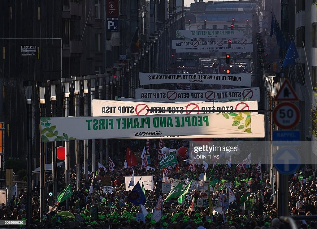 Demonstrators hold banners and flags as they demonstrate outside the European Union headquarters in Brussels, on September 20, 2016 to protest against huge transatlantic trade deals linking Europe with Canada and the United States. Several thousand The protests came after mass rallies in German cities on September 17, 2016 against the European Union's planned Transatlantic Trade and Investment Partnership (TTIP) with the United States, and the Comprehensive Economic and Trade Agreement (CETA) with Canada. / AFP / JOHN