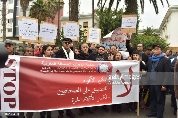 Demonstrators hold banners and placards as they gather outside the Court of General Sessions to stage a protest against the trial of four journalists...