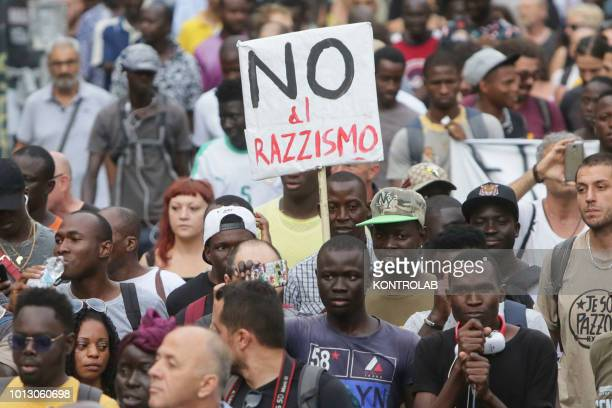 Demonstrators hold banners and shout slogans against racism during a rally in solidarity with a migrant from Senegal wounded by pistol shot in the...