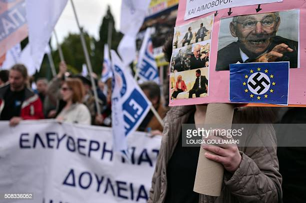 Demonstrators hold banners during a massive protest beside the Greek parliament during a massive protest on February 4 2016 Thousands of people...