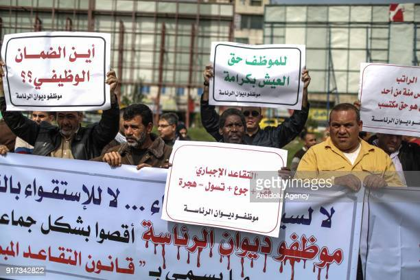 Demonstrators hold banners during a protest by public servants against the pay deductions and early retirement decision of the government at Saraya...