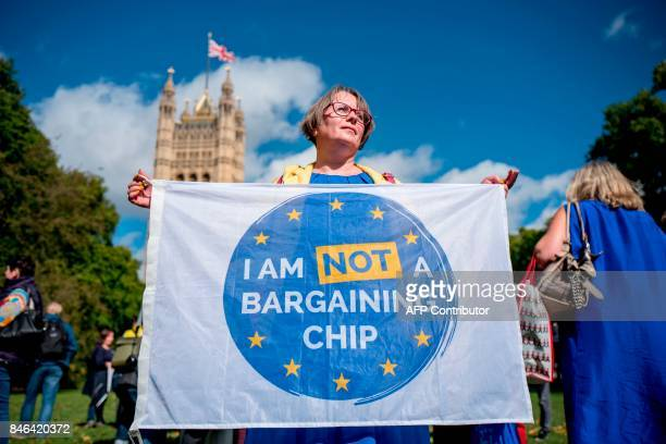 Demonstrators hold banners during a protest to Lobby MPs to guarantee the rights of EU citizens living in the UK after Brexit outside the Houses of...