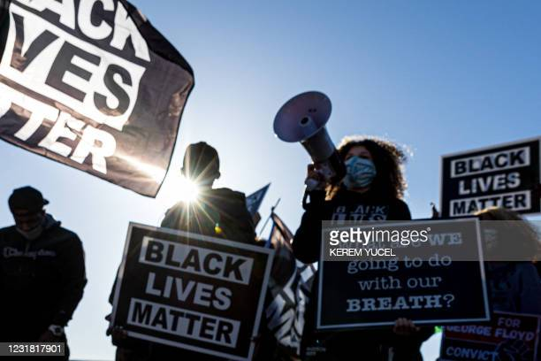 """Demonstrators hold """"Black Lives Matter"""" signs as they participate in the """"Justice for George Floyd"""" march outside the Minnesota State Capitol on..."""
