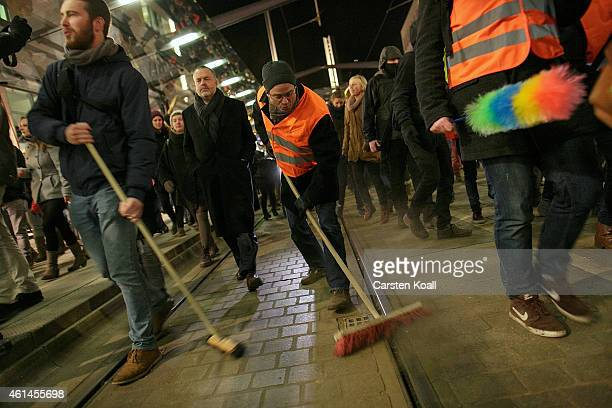 Demonstrators hold brooms in a symbolic gesture to sweep away racism and intolerance as Pegida supporters make their weekly march on January 12 2015...
