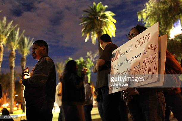 Demonstrators hold candles and protest signs during a vigil protesting Arizona's new immigration law outside the Arizona State Capitol building on...