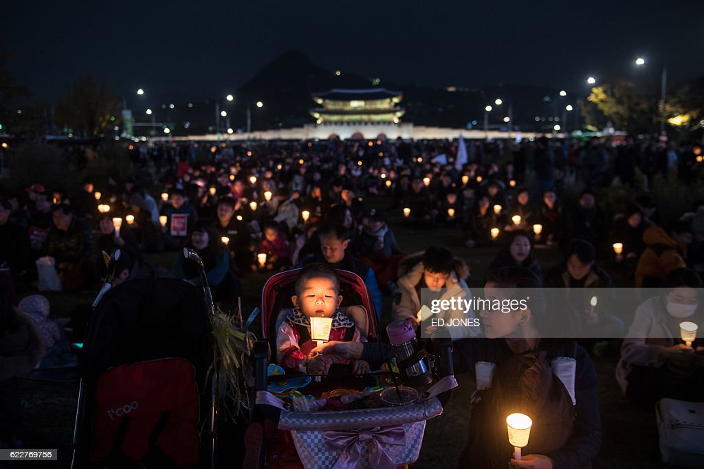 TOPSHOT - Demonstrators hold candles during an anti-government protest in the Gwanghwamun area of central Seoul on November 12, 2016. Up to one million people were expected to take to the streets of Seoul to demand the resignation of scandal-hit President Park Geun-Hye, in one of the largest anti-government protests in decades. / AFP / Ed JONES