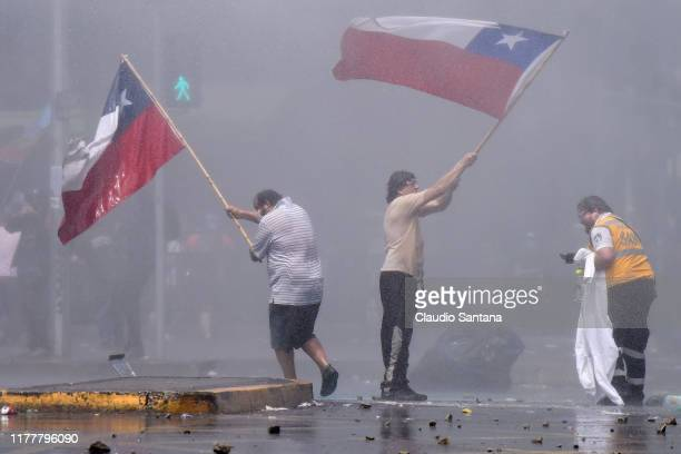 Demonstrators hold Chilean flags as clashing with riot police during the sixth day of protests against President Sebastian Piñera on October 23 2019...