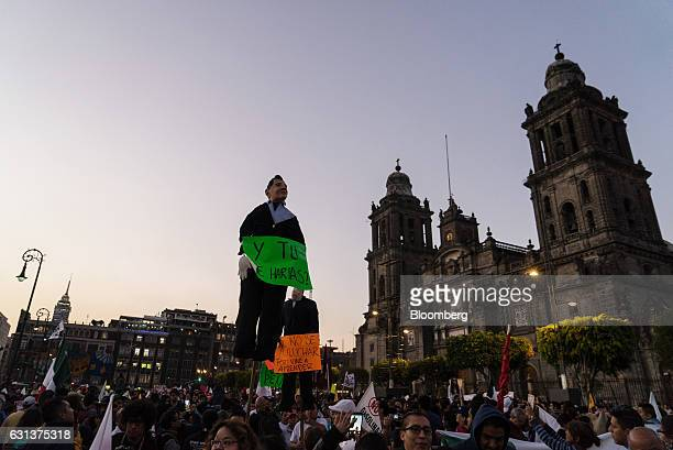 Demonstrators hold effigies of Mexico's President Enrique Pena Nieto front and US Presidentelect Donald Trump rear during a protest against the...