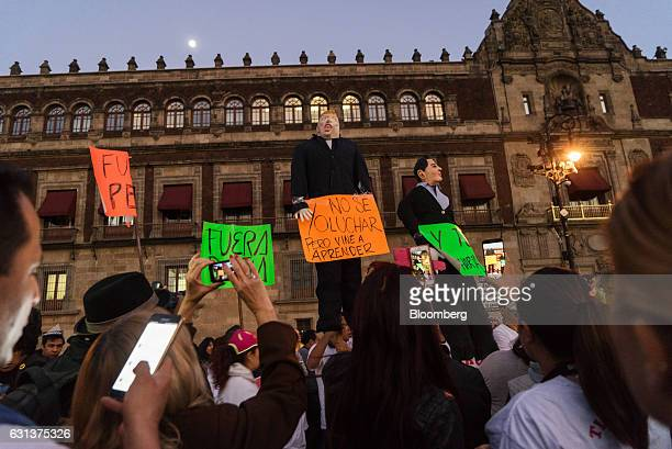 Demonstrators hold effigies of Mexico's President Enrique Pena Nieto right and US Presidentelect Donald Trump during a protest against the gasoline...