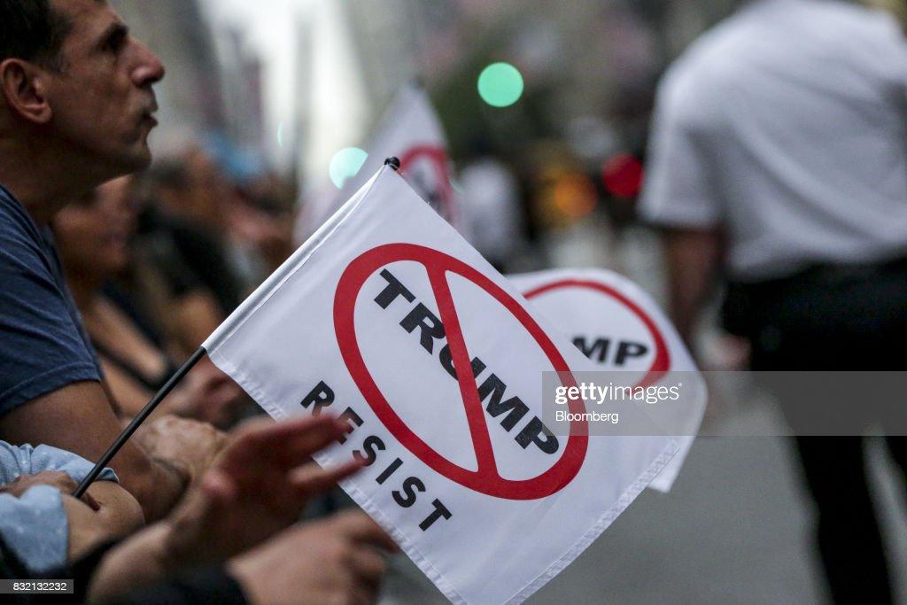Demonstrators hold flags during the 'Defend DACA & TPS' rally outside of Trump Tower in New York, U.S., on Tuesday, Aug. 15, 2017. A day after belatedly faulting white supremacists for deadly clashes in Virginia, President Donald Trump returned to his controversial position that there was 'blame on both sides' for the weekend violence, saying that liberal counter-protesters also bore responsibility. Photographer: Jeenah Moon/Bloomberg via Getty Images