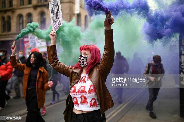 Demonstrators hold flares as they protest against the Police, Crime, Sentencing and Courts Bill 2021 in central Manchester on May 1, 2021. - Previous...