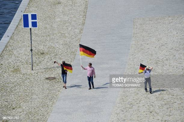 Demonstrators hold German flags along the river Spree during the demonstration for the future of Germany called by the farright AfD in Berlin on May...