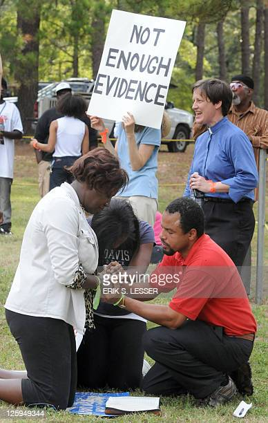Demonstrators hold hands and pray as they call for Georgia state officials to halt the scheduled execution of convicted cop killer Troy Davis at the...