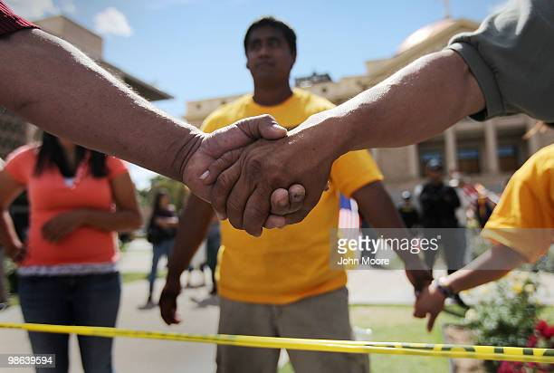 Demonstrators hold hands while protesting a new immigration law outside the Arizona State Capitol building on April 23 2010 in Phoenix Arizona...