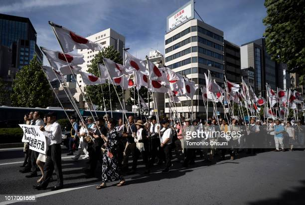 Demonstrators hold Japanese national flags during a march near the Yasukuni Shrine on August 15 2018 in Tokyo Japan Japan marks the 73rd anniversary...
