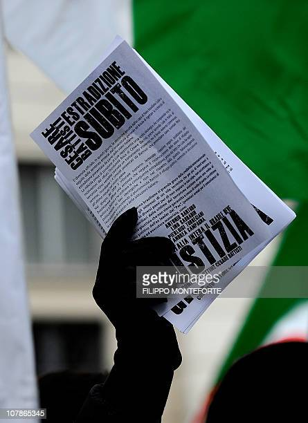 """Demonstrators hold leaflets reading """"Extradition now"""" in front of Brazil's embassy to protest Brazilian President Lula's refusal to extradite..."""