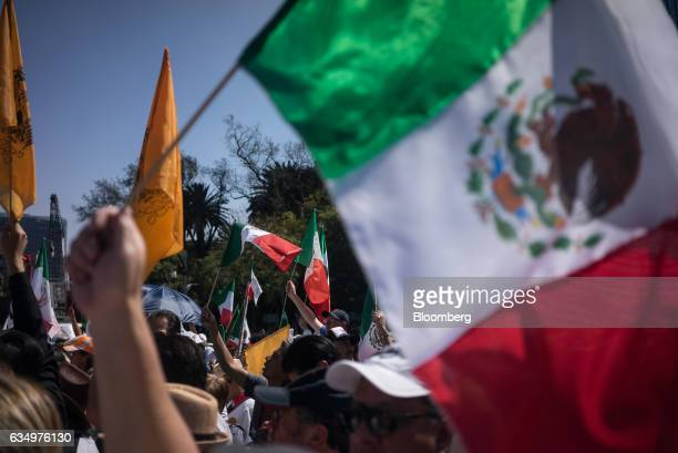 Demonstrators hold Mexican flags during a protest to demand the Mexican government defend the country in the face of US President Donald Trump's...