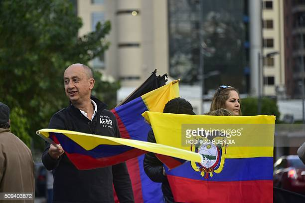 Demonstrators hold national flags as they protest against the government of Ecuadorean President Rafael Correa in Quito on February 10 2016 AFP PHOTO...