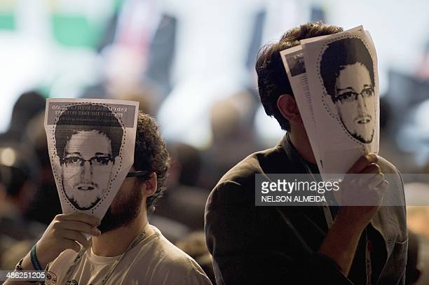 Demonstrators hold papers to be cut to make portraits of Edward Snowden in front of their own faces ai a protest during the opening ceremony during...