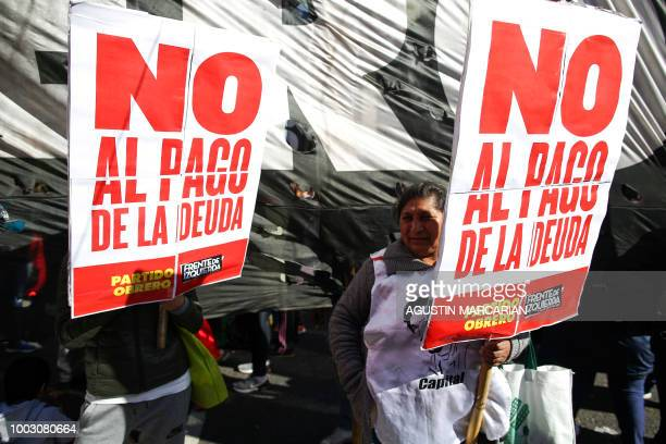 Demonstrators hold placards against the debt payment during a protest against Argentina's latest agreement with the International Monetary Fund in...