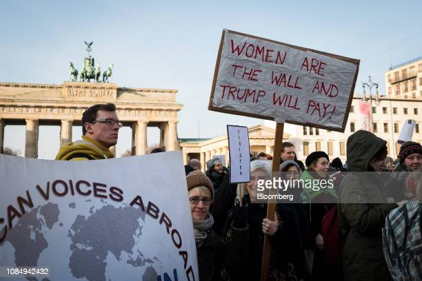 Demonstrators hold placards and banners during the Berlin chapter of the Women's March Global near the Brandenburg Gate in Berlin Germany on Saturday...