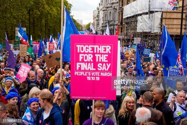 Demonstrators hold placards and EU and Union flags as they take part in a march by the People's Vote organisation in central London on October 19...