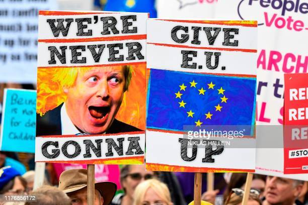 TOPSHOT Demonstrators hold placards and EU and Union flags as they take part in a march by the People's Vote organisation in central London on...