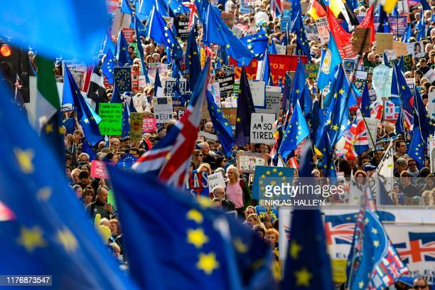 Demonstrators hold placards and EU flags as they take part in a march by the People's Vote organisation in central London on October 19 calling for a...