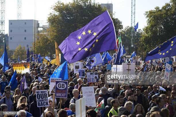 Demonstrators hold placards and European Union flags as they take part in a march calling for a People's Vote on the final Brexit deal in central...