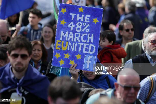 Demonstrators hold placards and wave EU flags as they participate in an anti Brexit proEuropean Union march in London on March 25 ahead of the...