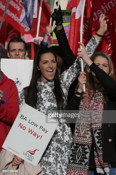 Demonstrators hold placards and wave flags as they protest against the low wages and 'poverty pay' of British Airways' staff outside the Houses of...
