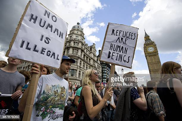 Demonstrators hold placards as pass the Houses of Parliament during a prorefugee rally in central London on September 12 2015 Tens of thousands of...