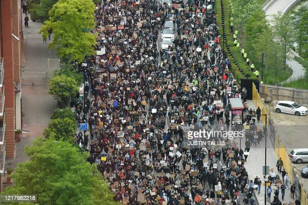Demonstrators hold placards as they attend a protest march to the US Embassy in London on June 6 to show solidarity with the Black Lives Matter...