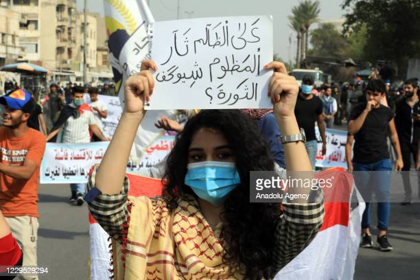 Demonstrators hold placards as they gather for an anti-government demonstration over corruption and poor services in Tahrir Square in the centre of...