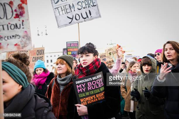 Demonstrators hold placards as they march during the Berlin chapter of the Women's March Global near the Brandenburg Gate in Berlin Germany on...