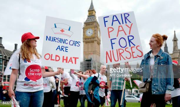 Demonstrators hold placards as they participate in a protest organised by nurses against the British government's pay cap on public sector workers...