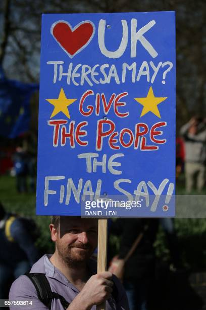 Demonstrators hold placards as they prepare to participate in an anti Brexit proEuropean Union march in London on March 25 ahead of the British...