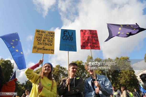 Demonstrators hold placards as they prepare to take part in a rally by the People's Vote organisation in central London on October 19 calling for a...