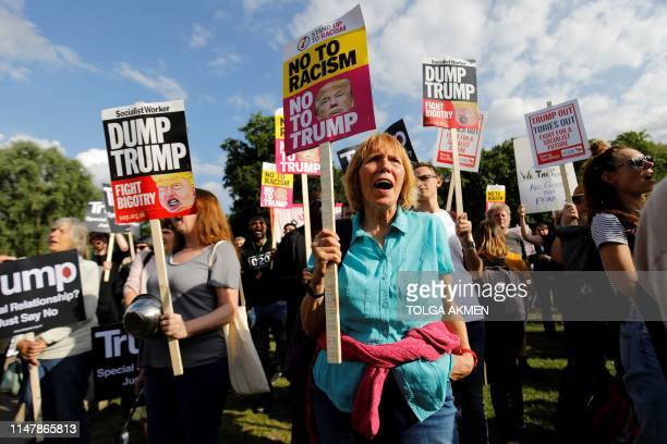 Demonstrators hold placards as they protest against US President Donald Trump's visit outside of Buckingham Palace in central London on June 3 on the...