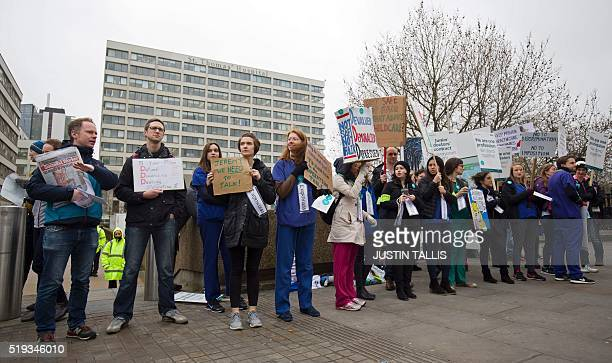 Demonstrators hold placards as they protest during a Junior Doctors' strike outside St Thomas' Hospital in central London on April 6 against proposed...