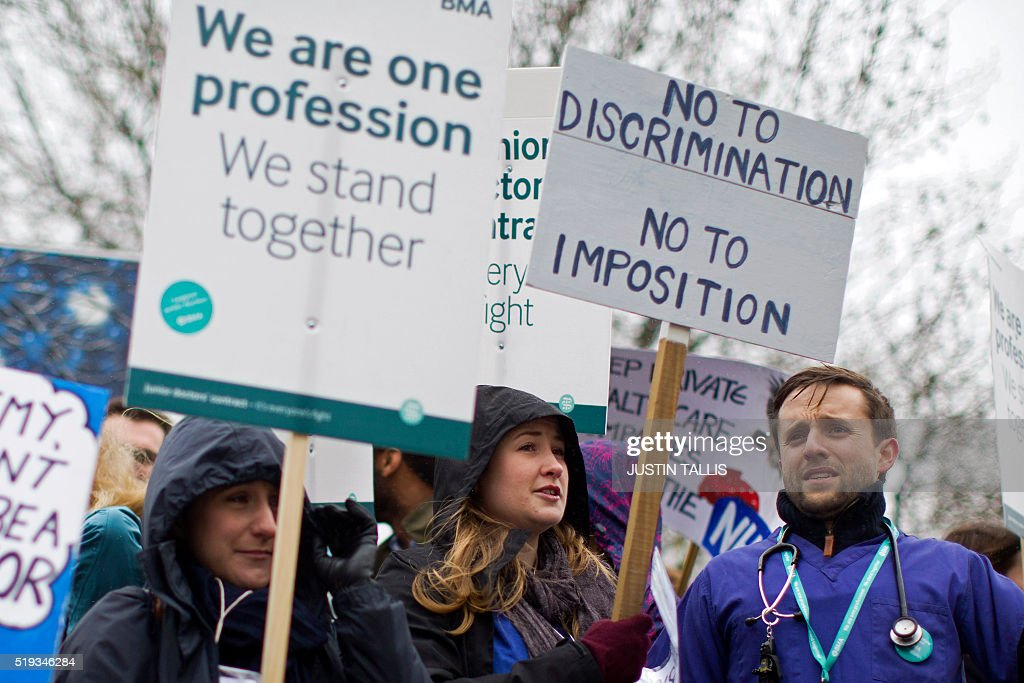 Demonstrators hold placards as they protest during a Junior Doctors' strike outside St Thomas' Hospital in central London on April 6, 2016, against proposed new conditions and pay rates for working unsociable hours. Thousands of operations and procedures across England have been cancelled as a result of the 48 hour strike which began Wednesday morning. / AFP / JUSTIN