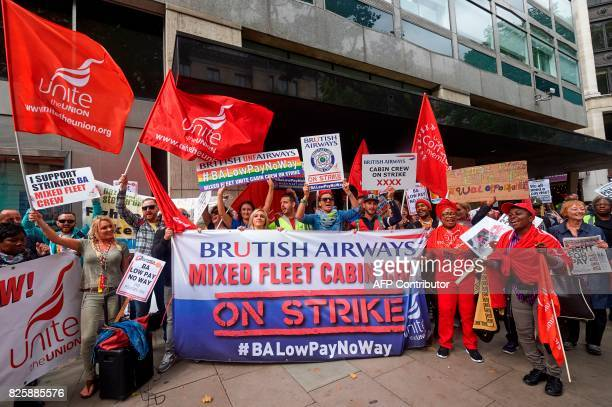 Demonstrators hold placards as they protest over against a British Airways mixed fleet cabin crew paydispute outside the Civil Aviation Authority in...