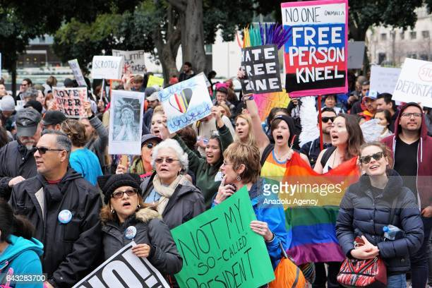 Demonstrators hold placards as they stage a Presidents Day protest in front of City Hall in Los Angeles USA on February 20 2017 The demonstration was...
