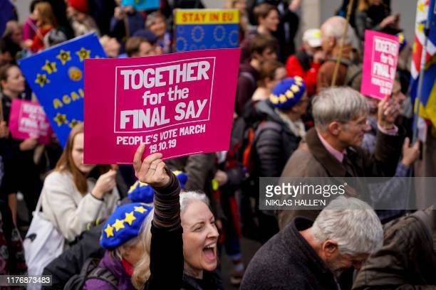 Demonstrators hold placards as they take part in a march by the People's Vote organisation in central London on October 19 calling for a final say in...