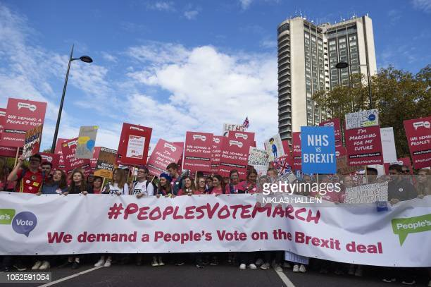 Demonstrators hold placards as they take part in a march calling for a People's Vote on the final Brexit deal in central London on October 20 2018...
