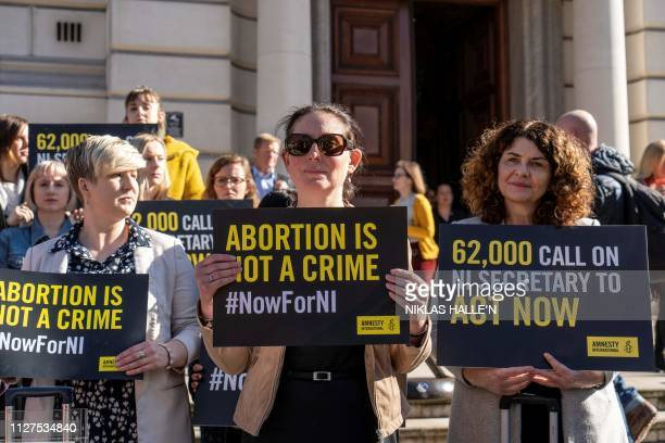 Demonstrators hold placards as they take part in a protest calling for change to Northern Ireland's abortion laws during a protest in central London...