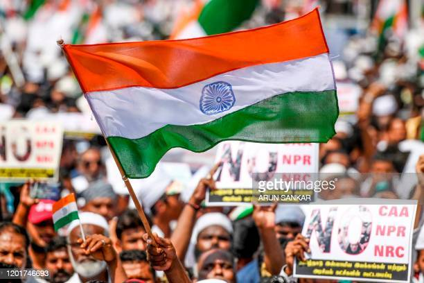 Demonstrators hold placards as they wave Indian national flags during a protest organised by various Muslim organisations and opposition parties...