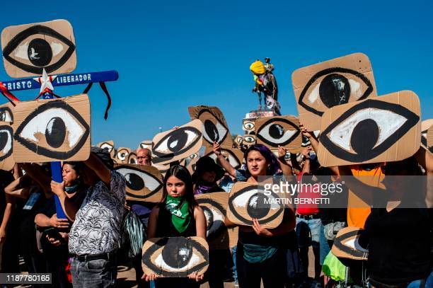 Demonstrators hold placards depicting eyes -in reference to police pellets reaching demonstrators' eyes- during a protest against Pinera's government...